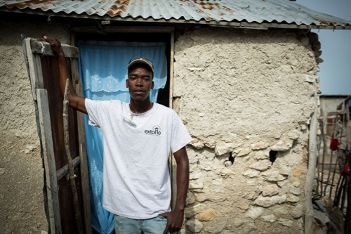 Haitian man in front of his home.